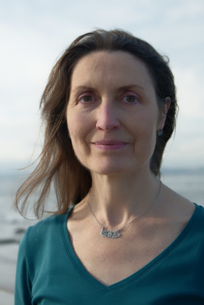 Portrait photo of Andrea St Clair with the sea in the background