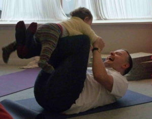 A father in a yoga class laughing with a baby
